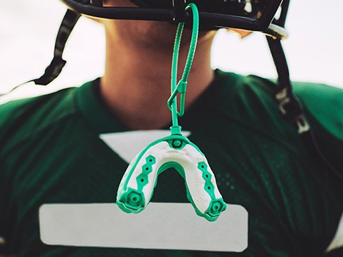 Mouthguard hanging from football helmet